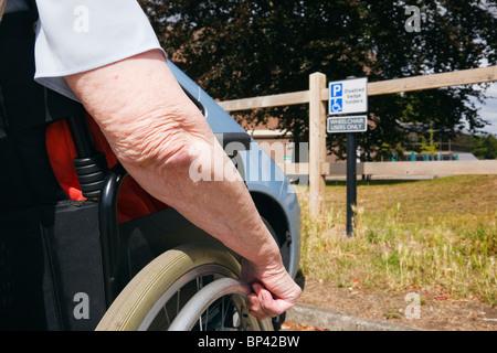Vieille Femme dans un fauteuil roulant par une voiture garée dans un parking handicapés badge bleu bay avec signe Banque D'Images