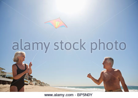 Senior couple flying kite on beach Banque D'Images