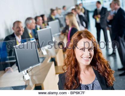 Une femme d'au centre de conférence de l'enregistrement, smiling Banque D'Images