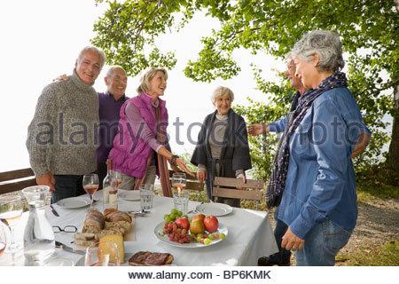 Trois couples d'aînés en train de déjeuner en plein air, chaque message d'autres Banque D'Images