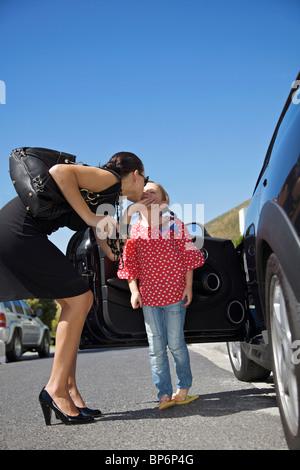 Une femme s'embrasser une fille debout à côté d'une voiture Banque D'Images