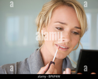 A young woman applying Lip Gloss Banque D'Images