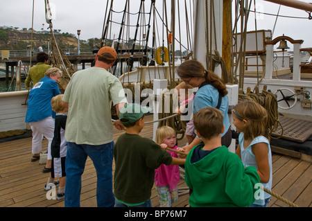 Les parents et les enfants de la famille tourisme corde de traction à bord du Pilgrim, Tall Ship à Dana Point Harbor, Banque D'Images