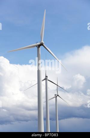 Les éoliennes contre le ciel bleu et les nuages blancs Banque D'Images