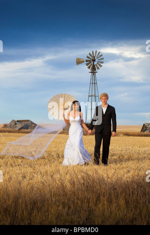 Three Hills, Alberta, Canada; une bride and groom posing in a farm field Banque D'Images