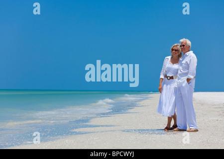 Happy senior man and woman couple ensemble face à la mer sur une plage tropicale déserte avec un ciel bleu clair Banque D'Images
