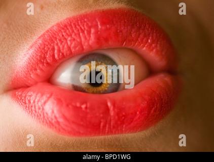 Close-up du globe oculaire à l'intérieur de la bouche avec des lèvres rose Banque D'Images