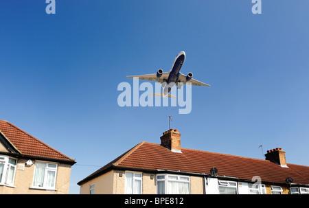 British Airways avion volant à basse altitude au-dessus house avant l'atterrissage Banque D'Images