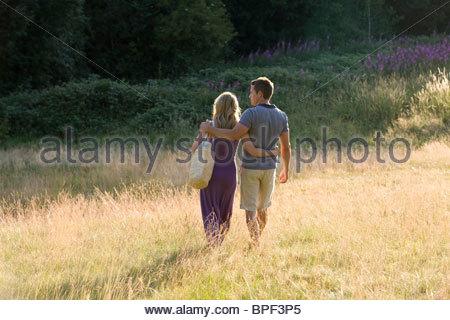 Un jeune couple en train de marcher à travers un champ bras dessus bras dessous, vue arrière Banque D'Images