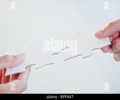 La connexion mains jigsaw puzzle pieces Banque D'Images