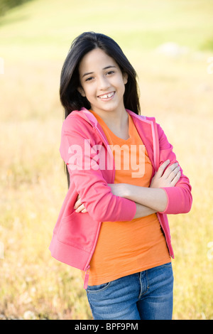 Young girl in field with arms crossed Banque D'Images