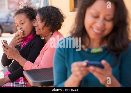 Femme hispanique de l'écoute d'un lecteur MP3 et sa mère et fille assis derrière elle, Boston, Massachusetts, USA Banque D'Images