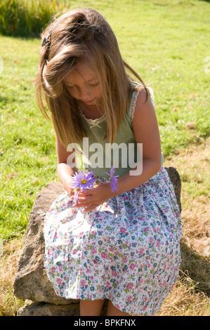 Little girl holding a bouquet de fleurs à l'extérieur