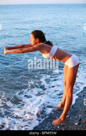 Belle brune faisant des exercices physiques sur la plage. Banque D'Images