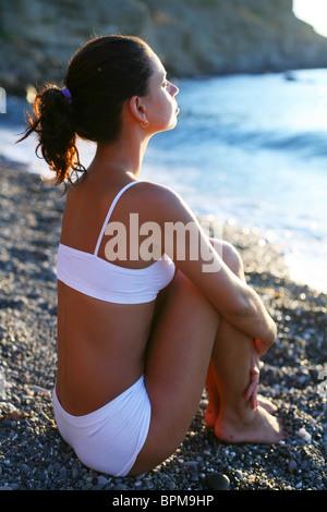 Femme méditant sur la plage au coucher du soleil. Banque D'Images