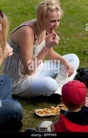 Assis sur l'herbe girl eating chips à un country fair Banque D'Images