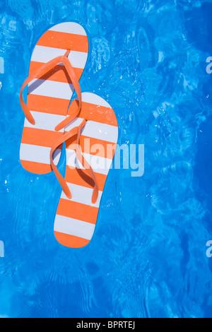 Jolie paire de tongs et de tongs stripey dans une piscine bleu pétillant Banque D'Images
