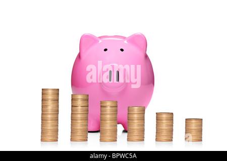 Pile de pièces en face de pink piggy bank en croissance Banque D'Images