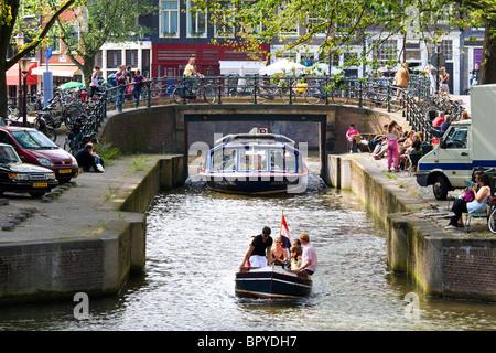 Amsterdam. Bateau de croisière du canal et dans le petit sloop Leliegracht Canal avec des terrasses de cafés. Les touristes assis et regarder.
