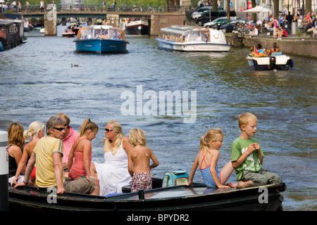 Amsterdam en bateau. Famille avec enfants en petit bateau ouvert sur le Canal Prinsengracht, avec canal bateaux d'excursion dans l'arrière-plan.