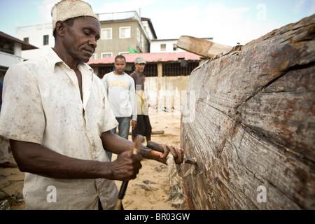 L'homme de la réparation d'un bateau en bois dans un chantier naval - Stonetown, Zanzibar, Tanzanie. Banque D'Images