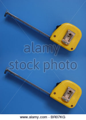 Vue rapprochée deux rubans à mesurer avec mètre blade montrant des chiffres légèrement étendu de cas sur fond bleu Banque D'Images
