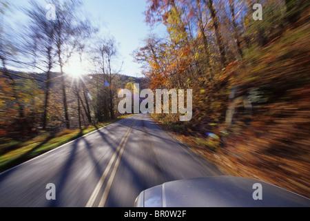 Flou de mouvement d'une voiture roulant le long d'une route de montagne près de Asheville, NC. Banque D'Images