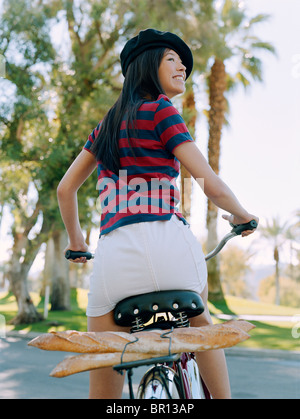 Woman riding bicycle avec beret et baguettes Banque D'Images