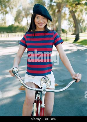 Woman riding bicycle avec beret Banque D'Images
