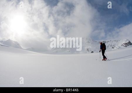 La skieuse de l'arrière-pays traverse sous feu glacier jour ciel d'orage. (Grand angle) Banque D'Images