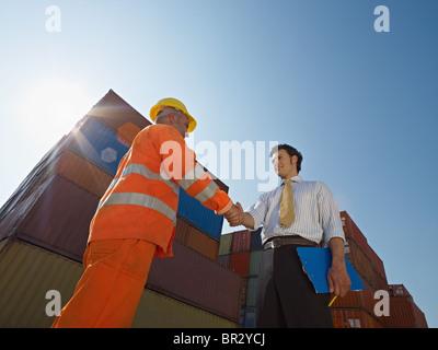 Travailleurs manuels et businessman shaking hands près de contenants d'expédition