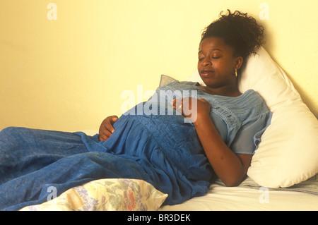 En gestation ethnic woman lying on a bed avec ses mains sur son ventre comme si elle se sent le bébé bouger Banque D'Images