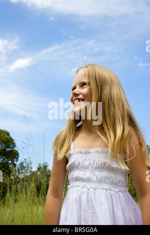 Little girl smiling and standing in a field against a blue sky Banque D'Images