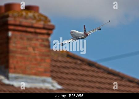 Un avion décollant de l'aéroport d'Heathrow à Londres, et survolant la zone de Stanwell Hounslow Borough. Banque D'Images