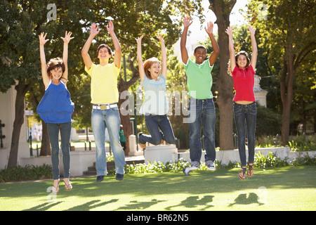 Groupe d'adolescents de sauter dans l'air In Park Banque D'Images