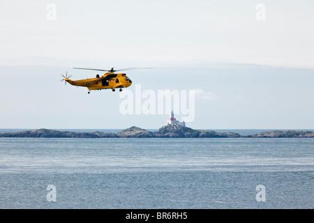 Hélicoptère de sauvetage de la RAF - Westland Sea King HAR3 sur la baie de l'Église, Anglesey. Le phare de Skerries Banque D'Images