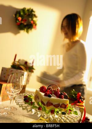 Gâteau de Noël sur la table, woman holding les plaques à l'arrière-plan, blurred motion