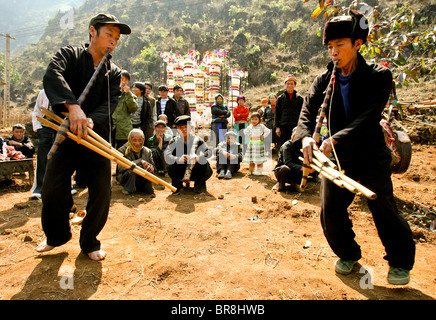 Les jeunes hommes Hmong jouant qeej, un instrument traditionnel, à un enterrement, le nord du Vietnam Banque D'Images