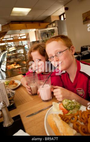 Lits jumeaux de 11 ans frère et sœur de boire des milkshakes à bientôt il l'étroite barre lait nationale, Aberystwyth Banque D'Images