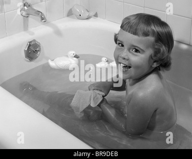 1950 SMILING LITTLE GIRL TAKING BAIGNOIRE DANS BAIGNOIRE LOOKING AT CAMERA Banque D'Images