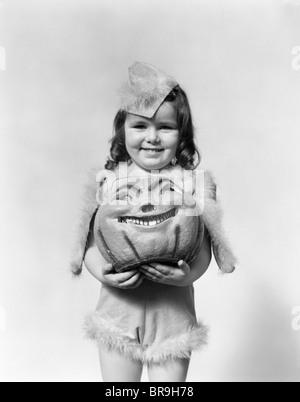 Années 1930 Années 1940 HAPPY SMILING LITTLE GIRL EN COSTUME tenant une tête de citrouille PAPIER MÂCHÉ Banque D'Images
