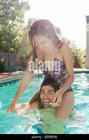 Jeune femme sur les épaules du jeune homme dans une piscine Banque D'Images