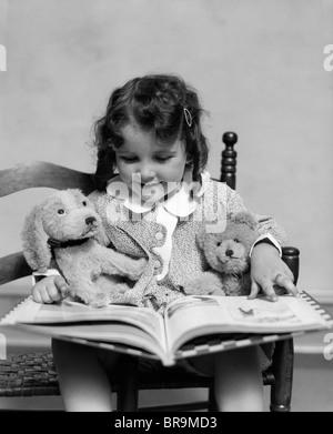 1930 GIRL READING STORYBOOK À SON JOUET CHIEN ET OURS Banque D'Images