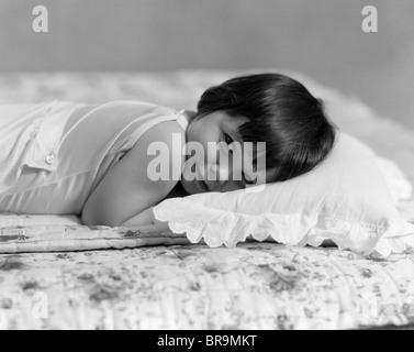 1930 Petite fille couchée la tête sur l'OREILLER LOOKING AT CAMERA Banque D'Images