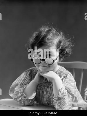 1930 PETITE FILLE PORTRAIT SMILING portant des lunettes rondes GRAND LOOKING AT CAMERA Banque D'Images