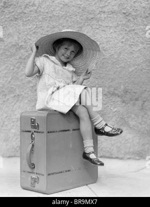 1930 PORTRAIT SMILING LITTLE GIRL SITTING ON SUITCASE PORT grand chapeau de paille Banque D'Images