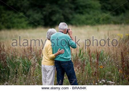 Un couple de prendre des photographies dans un champ Banque D'Images