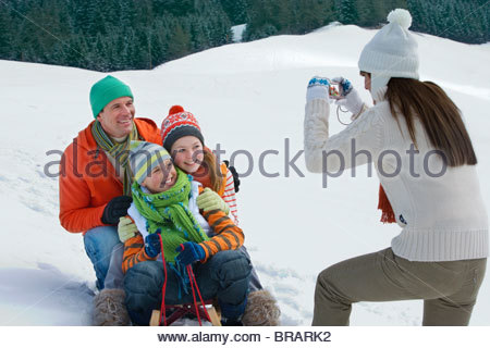 Mother taking picture of family sitting on ski slope Banque D'Images