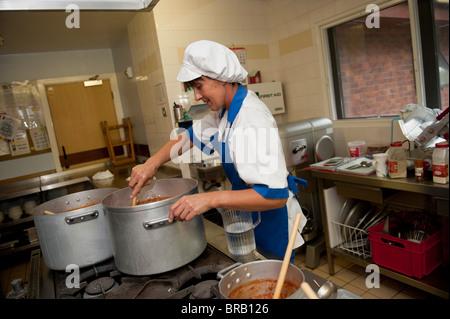 Cuisinier de l'école à préparer le dîner dans une cuisine de l'école primaire, UK Banque D'Images