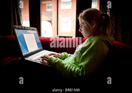 Adolescente de 16 ans d'étudier pour son GCSE examens sur son ordinateur portable à la maison, UK Banque D'Images